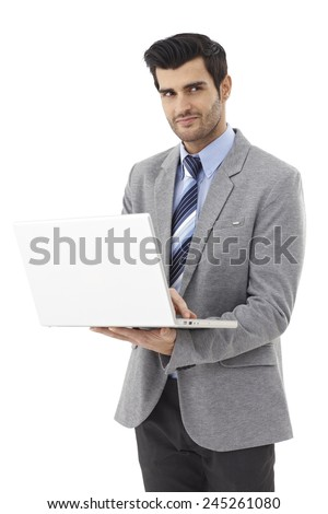 Young businessman holding laptop computer, looking away, standing. - stock photo