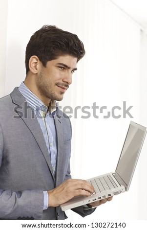 Young businessman holding laptop in hands, working.