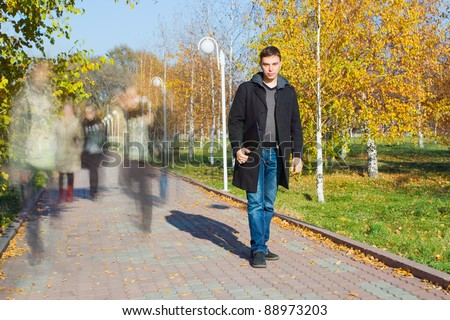 Young businessman holding laptop in the park. Motion blurred people walking along a path - stock photo