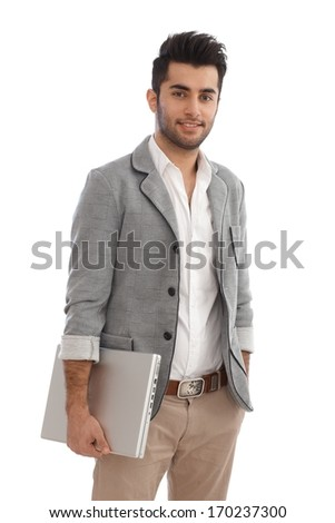 Young businessman holding laptop, standing with hands in pockets. - stock photo