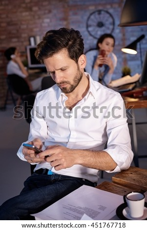 young businessman holding mobilephone in hand, writing text message, sitting at desk. - stock photo