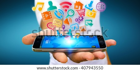 Young businessman holding modern digital icon application over his mobile phone - stock photo