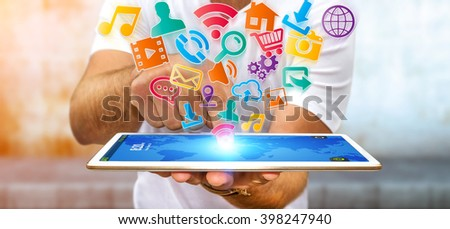 Young businessman holding modern digital icon application over his tablet - stock photo
