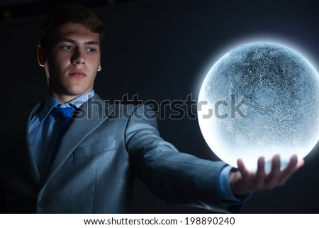 Young businessman holding moon planet in hand - stock photo