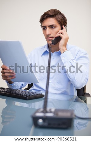 Young businessman holding paperwork while on the phone