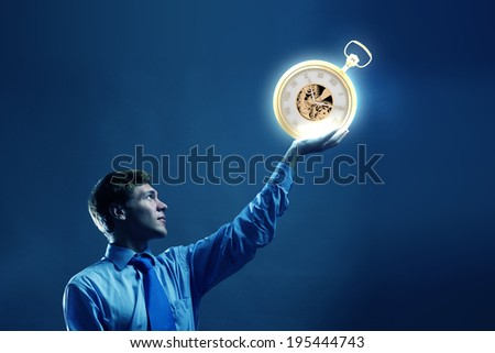 Young businessman holding pocket watch in hand