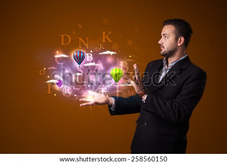 Young businessman holding shining letters and balloons in his hand - stock photo