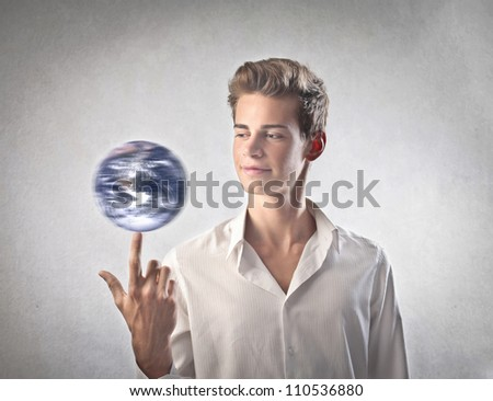 Young businessman holding the Earth on his forefinger [Elements of this image furnished by NASA] - stock photo