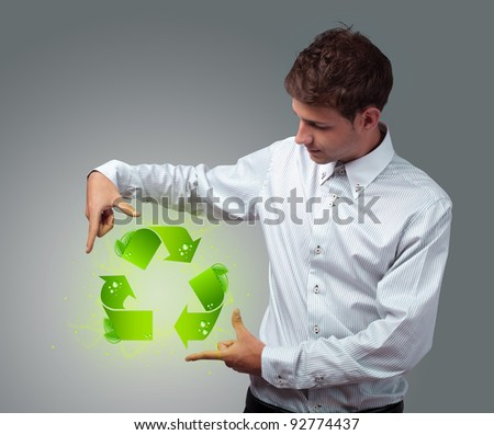 Young businessman holding virtual eco sign - stock photo