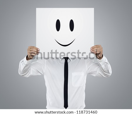 Young businessman holding white card with a happy face on it isolated on gray background - stock photo