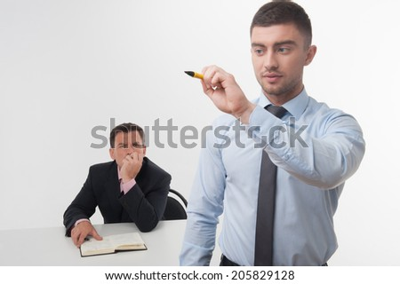 Young businessman holds marker writing, drawing something in the air with his skeptical chief on background isolated on white - stock photo