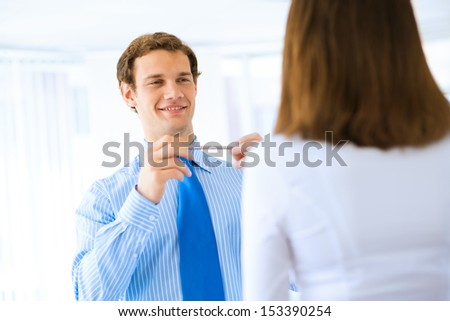 young businessman holds up a pen, talking with a colleague in front of - stock photo