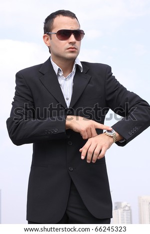 "Young businessman in a black suit showing ""time"" on sky background"