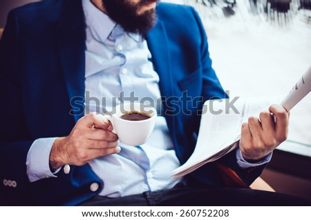 Young businessman in a blue jacket with a cup of coffee, reading a newspaper in a cafe - stock photo