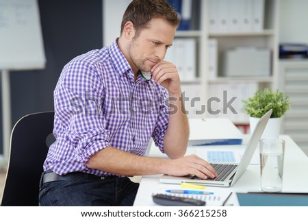 Young businessman in a checked shirt sitting working on a laptop at a table in the office with a thoughtful expression, side view - stock photo