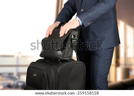 young businessman  in  a modern  stylish suit with  luggage  waiting  for plane in  the airport  - stock photo