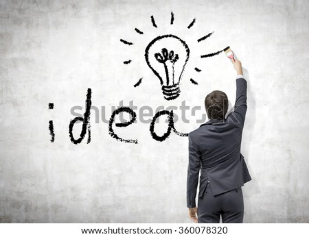 Young businessman in a suit painting the word 'idea' and a bulb with a brush in black on the concrete wall. Back view. Concept a new idea - stock photo