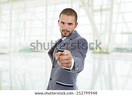 young businessman in a suit pointing with his finger at the office - stock photo