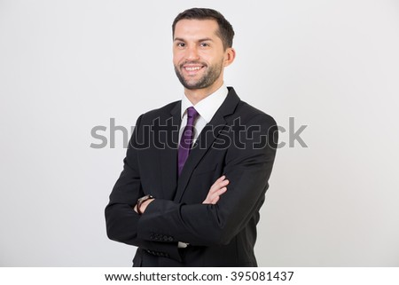 Young businessman in a suit smiling in a studio