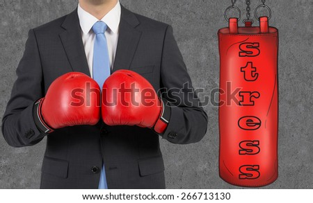 Young businessman in a suit wearing boxing gloves is ready to hit the punching bag - stock photo