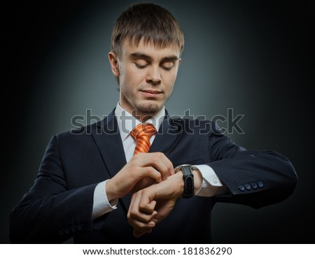 young businessman in black costume wind clock (wristwatch) on hand, closeup - stock photo