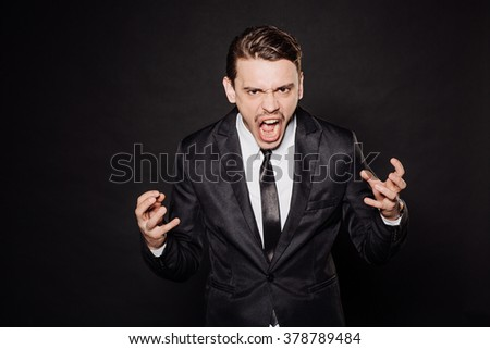 young businessman in black suit angry, shouts, lifting his hands up. emotions and people concept. image on a black studio background. - stock photo