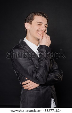 young businessman in black suit with a mischievous thoughtful expression. emotions and people concept. image on a black background. - stock photo