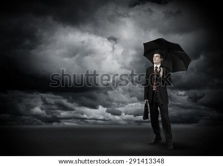 Young businessman in black suit with umbrella