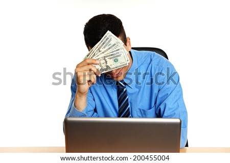 Young businessman in blue shirt thinking in office with money - stock photo
