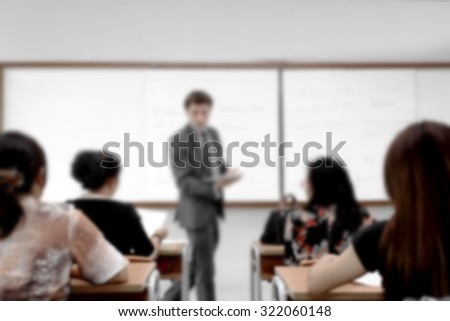 Young businessman in business classroom with young female students