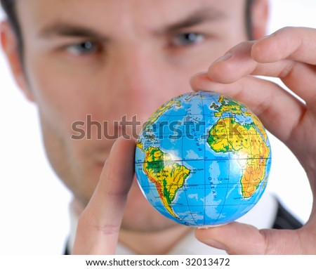 young businessman in  business suit holds model of globe in  hand and reflects
