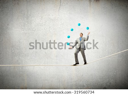 Young businessman in cap on stage juggling with balls - stock photo