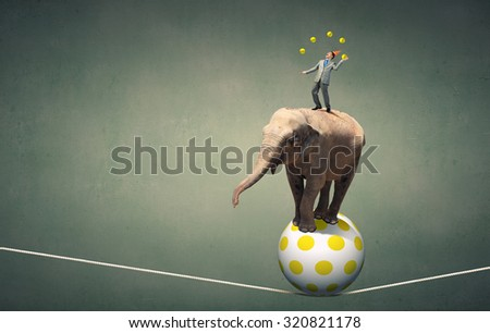 Young businessman in cap standing on elephant and juggling with balls - stock photo