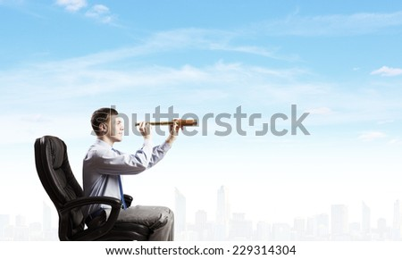Young businessman in chair looking in to spyglass - stock photo