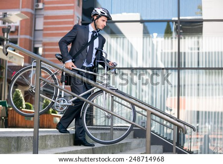 young businessman in crash helmet carrying bicycle down steps - stock photo