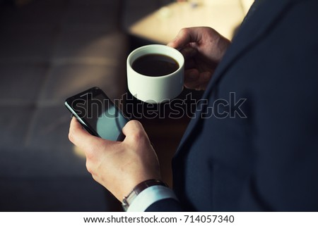 young businessman in dark office with smartphone tablet and coffee