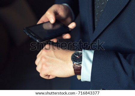young businessman in dark office with smartphone tablet and credit card