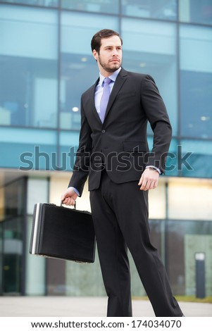 young businessman in front of an office building with a briefcase  - stock photo