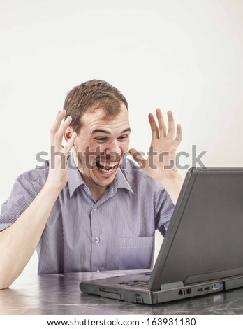 Young businessman in glasses merry and  looking at screen black laptop at desk in his office on background gray wall with clock  - stock photo