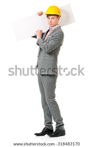 Young businessman in hard hat showing blank placard board, isolated on white background