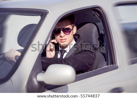 young businessman in his car at the wheel talking on a mobile phone