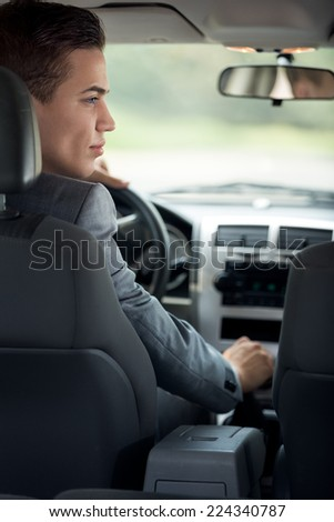 young businessman in his car, back view