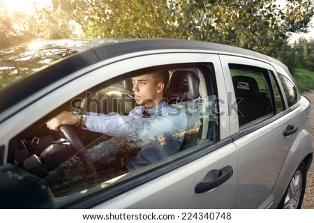 Young businessman in his car, side view  - stock photo