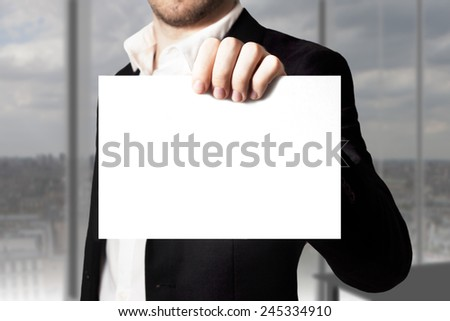 young businessman in office holding white empty sign - stock photo