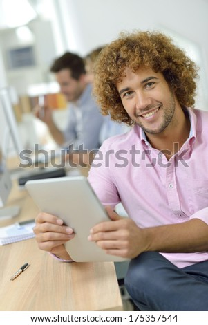 Young businessman in office working on tablet