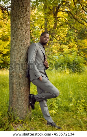 Young businessman in park near a tree