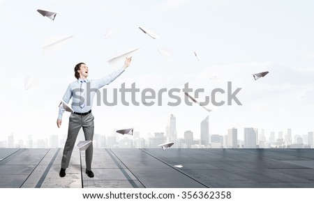 Young businessman in pile of books with paper plane in hand