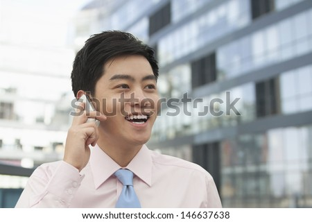 Young Businessman in pink button down shirt on the phone, Beijing, China - stock photo