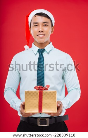 Young businessman in Santa hat holding a gift box - stock photo