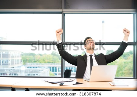 Young businessman in shirt and tie working on laptop at the office - stock photo